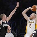 Los Angeles Lakers center Chris Kaman, right, puts up a shot as Brooklyn Nets forward Mason Plumlee defends during the first half of an NBA basketball game, Sunday, Feb. 23, 2014, in Los Angeles The Associated Press