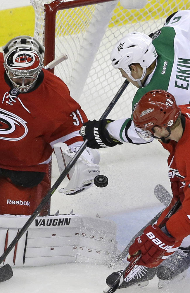 Carolina Hurricanes goalie Anton Khudobin (31), of Kazakhstan, blocks Dallas Stars' Cody Eakin (20) as Hurricanes' Eric Staal (12) defends during the third period of an NHL hockey game in Raleigh, N.C., Thursday, April 3, 2014. Carolina won 4-1