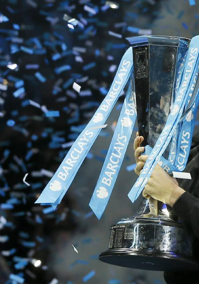 Novak Djokovic of Serbia kisses the ATP World Tour Finals tennis trophy as he poses for photographers after defeating Rafael Nadal of Spain at the O2 Arena in London, Monday, Nov. 11, 2013