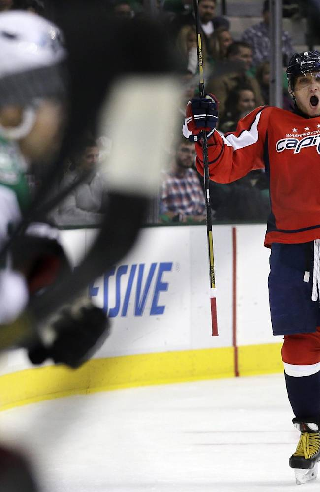 The Dallas Stars bench, left, watches as Washington Capitals' Alex Ovechkin (8), of Russia, celebrates his goal against them in the first period of an NHL hockey game on Saturday, Oct. 5, 2013, in Dallas