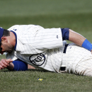 Chicago Cubs right fielder Justin Ruggiano holds his leg in the ninth inning of a baseball game against the Arizona Diamondbacks at Wrigley Field in Chicago on Wednesday, April 23, 2014 The Associated Press