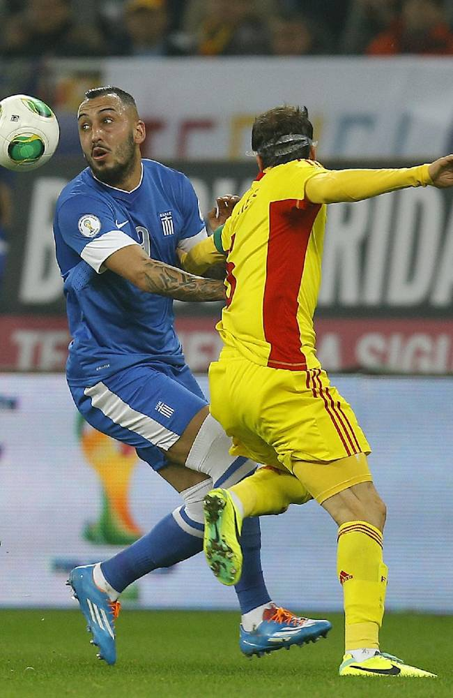 Greece's Kostas Mitroglou, left, and Romania's Vlad Chiriches challenge for the ball during their World Cup qualifying playoff second leg soccer match at the National Arena in Bucharest, Tuesday, Nov. 19, 2013
