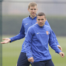Arsenal's German players Per Mertesacker, left, and Lukas Podolski talk during a training session at their London Colney training ground, Monday, March 10, 2014. Arsenal will play in a Champions League last sixteen second leg soccer match against Munich i