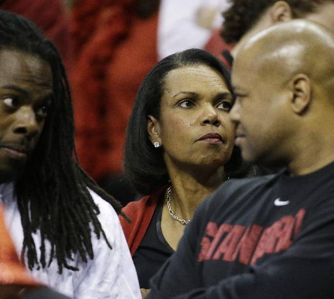 Former U.S. Secretary of State Condoleezza Rice, center watches play between Dayton and Stanford during the first half in a regional semifinal game at the NCAA college basketball tournament, Thursday, March 27, 2014, in Memphis, Tenn