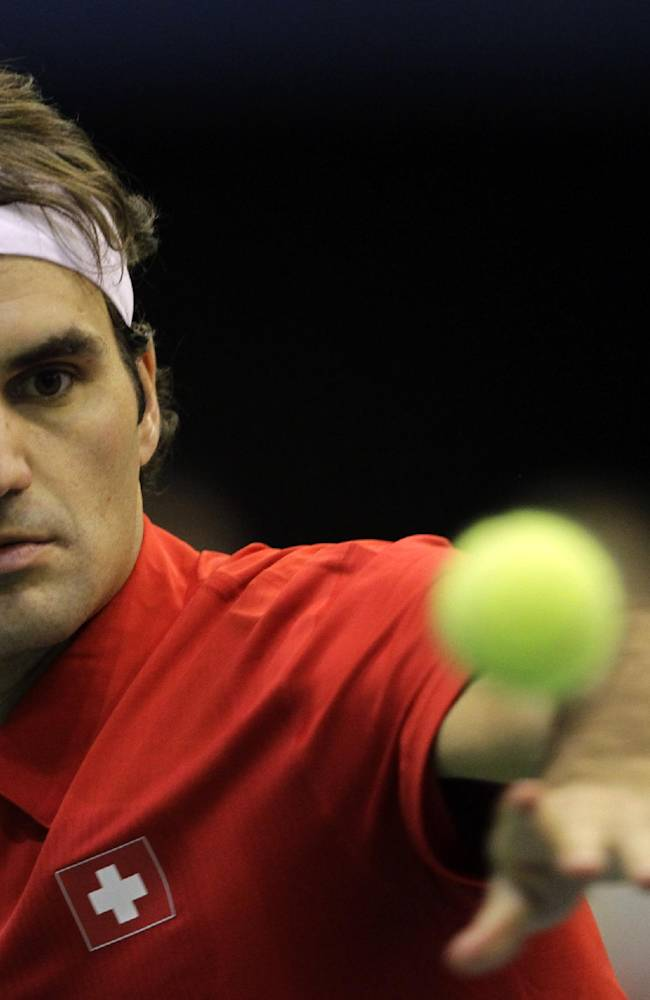 Switzerland's Roger Federer returns the ball against Ilija Bozoljac of Serbia during their Davis Cup World Group play-off first round tennis match between Serbia and Switzerland, in Novi Sad, Serbia, Friday, Jan. 31, 2014