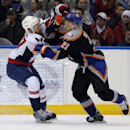 Washington Capitals defenseman Karl Alzner (27) checks New York Islanders right wing Kyle Okposo (21) during the second period of an NHL hockey game in Uniondale, N.Y., Saturday, Nov. 30, 2013 The Associated Press