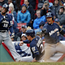 Milwaukee Brewers' Scooter Gennett (2) slides safely into home, scoring on a double by Lyle Overbay, as Khris Davis (18) and Carlos Gomez (27) react in the ninth inning of a baseball game against the Boston Red Sox at Fenway Park in Boston, Friday, April