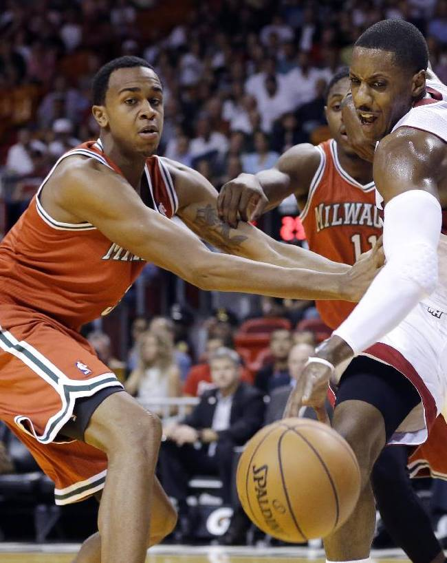 Miami Heat's Mario Chalmers, right, fights for control of the ball as Milwaukee Bucks' Caron Butler, left, and Brandon Knight, center, defend during the first half of an NBA basketball game Tuesday, Nov. 12, 2013, in Miami