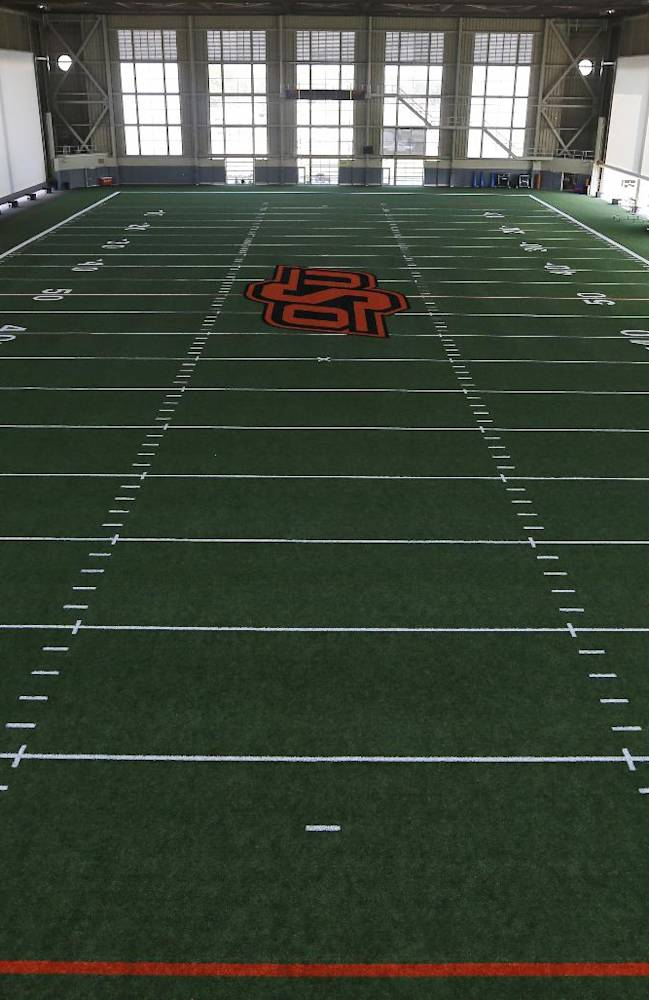 This Sept. 5, 2013 photo shows the indoor football practice facility at Oklahoma State University in Stillwater, Okla. Call them football palaces, and no college football program can call itself big-time without one that will leave recruits wide-eyed