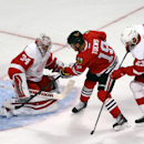Chicago Blackhawks' Jonathan Toews shoots wide of Detroit Red Wings goalie Petr Mrazek during the third period as Detroit's Brian Lashoff tries to check Toews during the third period of an NHL exhibition hockey game in Chicago on Tuesday, Sept. 23, 2014.