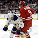 Carolina Hurricanes' Jay McClement (18) and Buffalo Sabres' Zemgus Girgensons (28), of Latvia, try to control the puck during the first period of an NHL hockey game in Raleigh, N.C., Thursday, Jan. 8, 2015 The Associated Press