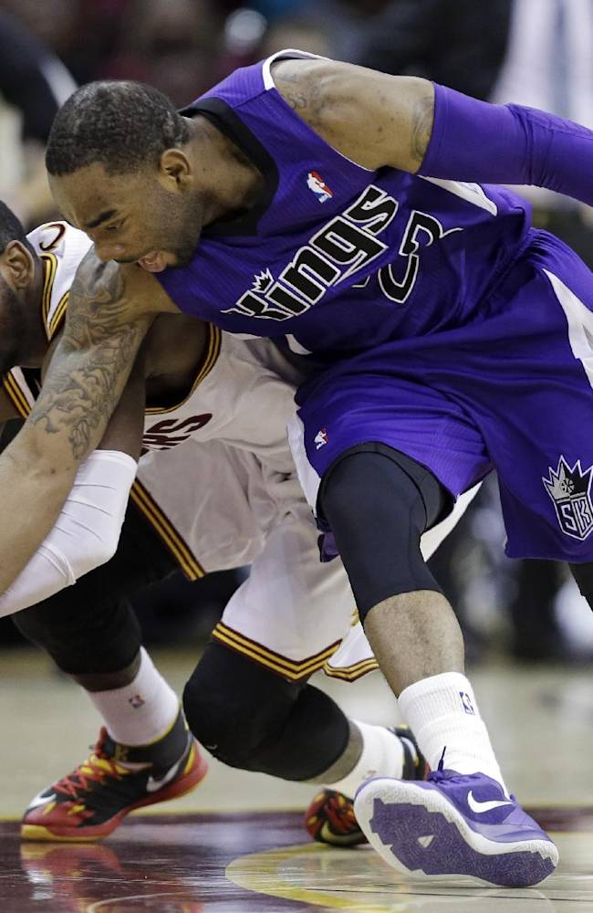 Cleveland Cavaliers' Kyrie Irving, left, and Sacramento Kings' Marcus Thornton chase down a loose ball during the third quarter of an NBA basketball game Tuesday, Feb. 11, 2014, in Cleveland. The Cavaliers won 109-99