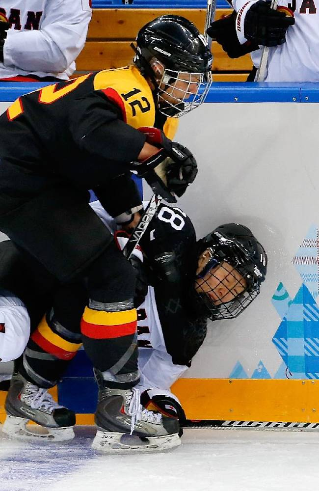 Susann Gotz of Germany and Tomoko Sakagami of Japan collide against the boards during the first period of the 2014 Winter Olympics women's ice hockey game at Shayba Arena, Tuesday, Feb. 18, 2014, in Sochi, Russia