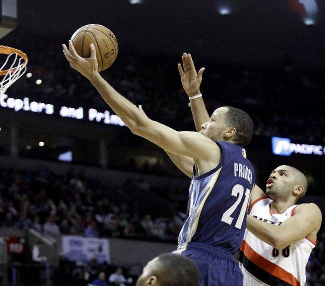Memphis Grizzlies forward Tayshaun Prince, left, drives to the hoop past Portland Trail Blazers forward Nicolas Batum, of France, during the first half of an NBA basketball game in Portland, Ore., Tuesday, Jan. 28, 2014