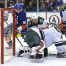 New York Islanders center John Tavares (91) scores a goal as Minnesota Wild goalie Devan Dubnyk (40) is down and Justin Fontaine (14) looks watches during the second period of an NHL hockey game Tuesday, March 24, 2015, in Uniondale, N.Y. (AP Photo/Paul Bereswill)