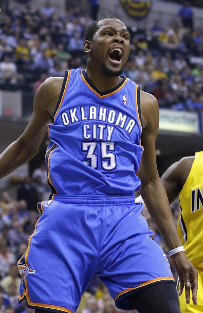 Oklahoma City Thunder forward Kevin Durant reacts after a dunk in front of Indiana Pacers center Ian Mahinmi in the first half of an NBA basketball game in Indianapolis, Sunday, April 13, 2014