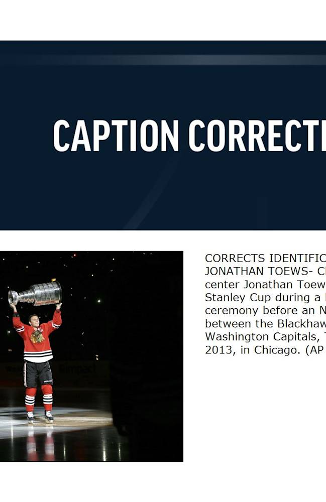 CORRECTS IDENTIFICATION OF JONATHAN TOEWS- Chicago Blackhawks center Jonathan Toews carries out the Stanley Cup during a banner raising ceremony before an NHL hockey game between the Blackhawks and the Washington Capitals, Tuesday, Oct. 1, 2013, in Chicago