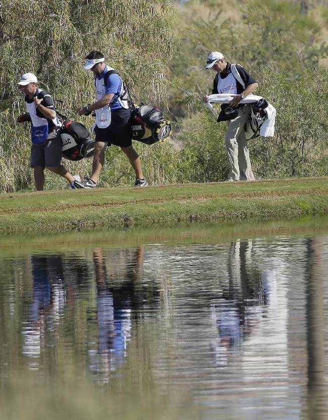 Japan's Ryo Ishikawa, right, walks along the 18th fairway after teeing off with Bill Hurley III and Brooks Koepka in the first round of the Shriners Hospitals for Children Open golf tournament, Thursday, Oct. 17, 2013, in Las Vegas