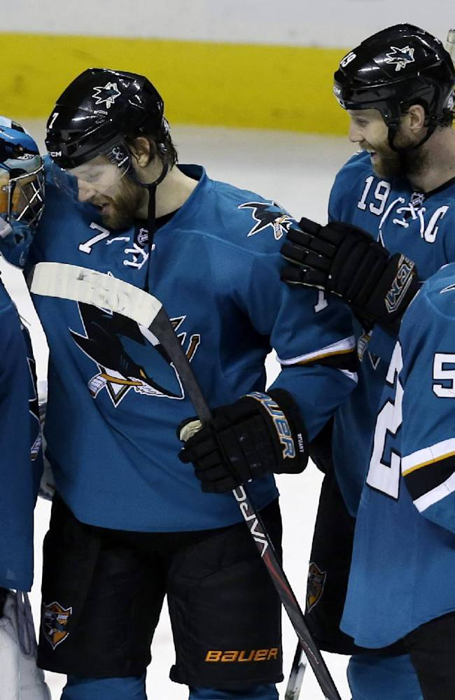 From left, San Jose Sharks goalie Alex Stalock, Brad Stuart, Joe Thornton and Matt Irwin celebrate after a 3-2 win over the Dallas Stars during the shootout of an NHL hockey game on Saturday, Dec. 21, 2013, in San Jose, Calif