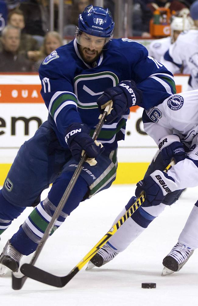 Vancouver Canucks' Ryan Kesler, left, stick-handles around Tampa Bay Lightning's Martin St. Louis during the first period of an NHL hockey game in Vancouver, British Columbia, on Wednesday, Jan. 1, 2014