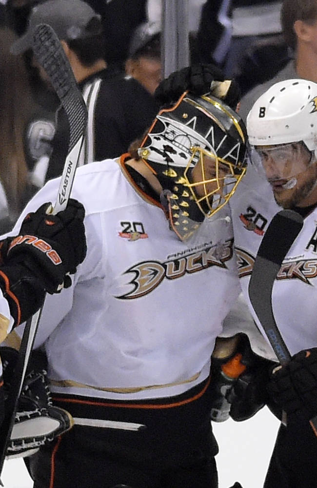 Anaheim Ducks goalie Jonas Hiller, center, of Switzerland, is congratulated by right wing Teemu Selanne, right, of Finland, and defenseman Ben Lovejoy after Game 3 of an NHL hockey second-round Stanley Cup playoff series against the Los Angeles Kings, Thursday, May 8, 2014, in Los Angeles. The Ducks won 3-2
