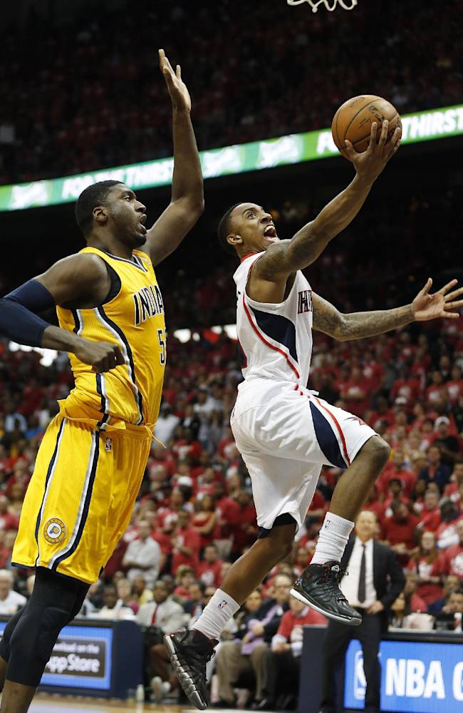 Atlanta Hawks guard Jeff Teague, right ,  scores as Indiana Pacers center Roy Hibbert (55) defends in the second half of Game 6 of a first-round NBA basketball playoff series in Atlanta, Thursday, May 1, 2014. Indiana won 95-88