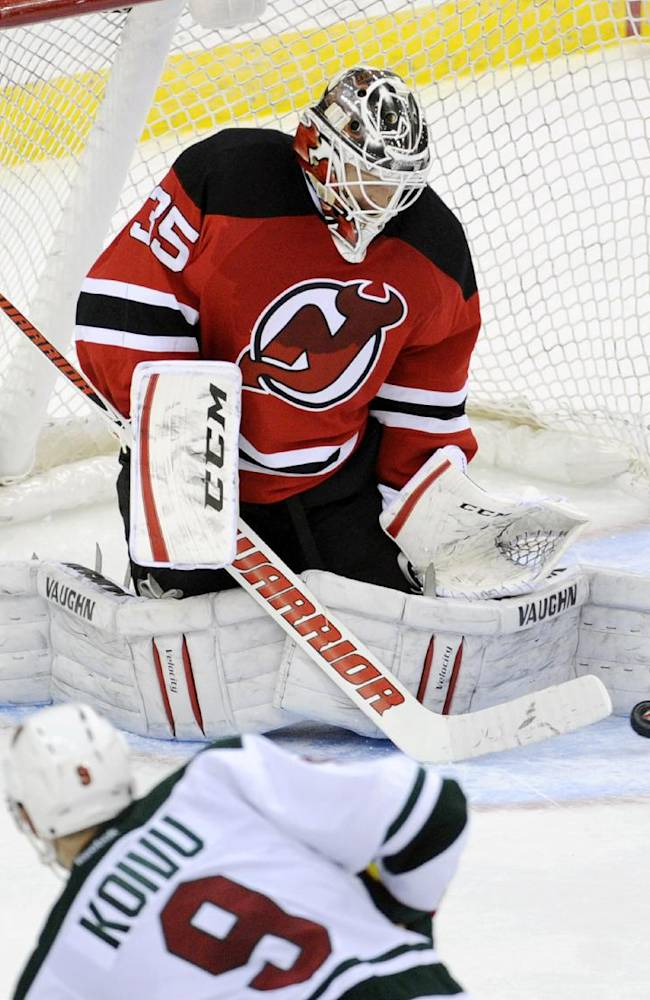 New Jersey Devils goaltender Cory Schneider deflects the puck as Minnesota Wild's Mikko Koivu (9) is near during the overtime period of an NHL hockey game Thursday, March 20, 2014, in Newark, N.J. The Devils won 4-3
