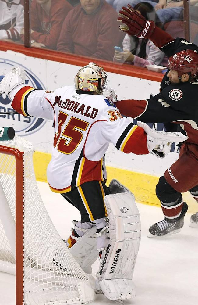 Calgary Flames' Joey MacDonald (35) collides with Phoenix Coyotes' David Moss (18) during the third period of an NHL hockey game on Tuesday Oct. 22, 2013, in Glendale, Ariz.  The Coyotes defeated the Flames 4-2