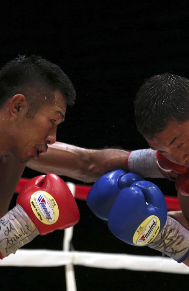 Japanese champion Takashi Uchiyama, left, sends a left into the face of compatriot challenger Daiki Kaneko in the 11th round of their WBA super featherweight boxing title bout in Tokyo, Tuesday, Dec. 31, 2013. Uchiyama defended his title by a unanimous decision