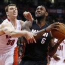 Miami Heat's LeBron James, right, is fouled by Toronto Raptors' Tyler Hansbrough during the first half of an NBA basketball game in Toronto, Friday, Nov. 29, 2013. (AP Photo/The Canadian Press, Mark Blinch)