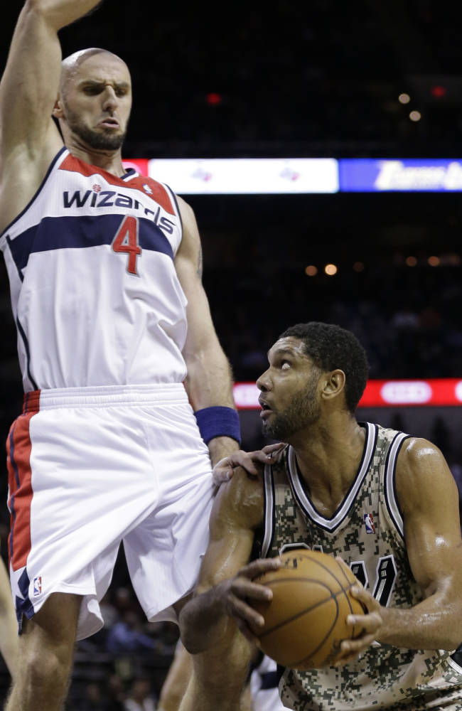 San Antonio Spurs' Tim Duncan, right, looks to shoot as Washington Wizards' Marcin Gortat (4) defends against him during the first half of an NBA basketball game on Wednesday, Nov. 13, 2013, in San Antonio
