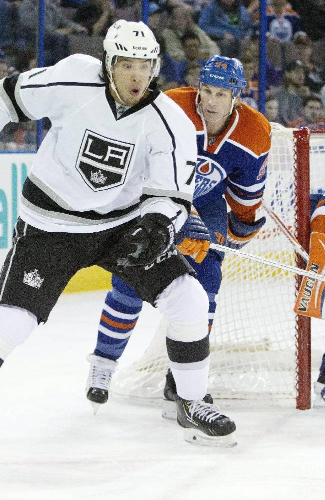 Los Angeles Kings Jordan Nolan (71) controls the puck as he is chased by Edmonton Oilers Ryan Smyth (94) and goalie Ben Scrivens (30) looks for the shot during first period NHL hockey action in Edmonton, Canada, Sunday March 9, 2014