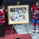 Montreal Canadiens' Tomas Plekanec and Andrei Markov, right, unveil a painting offered to former Montreal Canadiens captain Saku Koivu during a ceremony honoring his career Thursday, Dec. 18, 2014 in Montreal. Looking on is his wife Hanna and daughter Ilo
