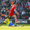 Southampton's Rickie Lambert, top, shoots past Newcastle United's Mapou Yanga-Mbiwa during their English Premier League soccer match at St Mary's, Southampton, England, Saturday, March 29, 2014
