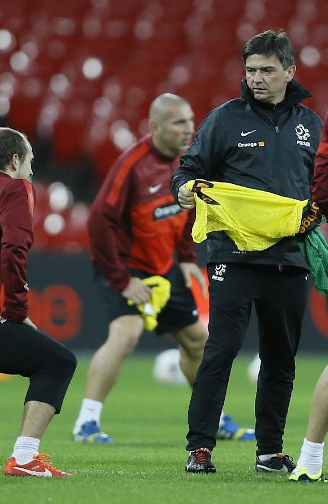 Poland's soccer team coach Waldemar Fornalik, second right, hands out bibs during a training session at Wembley Stadium in London, Monday, Oct. 14, 2013. England will play Poland in a World Cup Group H qualification match at Wembley stadium in London on Tuesday