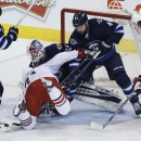 Columbus Blue Jackets' Nick Foligno (71) crashes into Winnipeg Jets goaltender Michael Hutchinson (34) as Dustin Byfuglien (33) and Zach Bogosian (44) defend during the first period of an NHL hockey game Wednesday, Jan. 21, 2015, in Winnipeg, Manitoba The