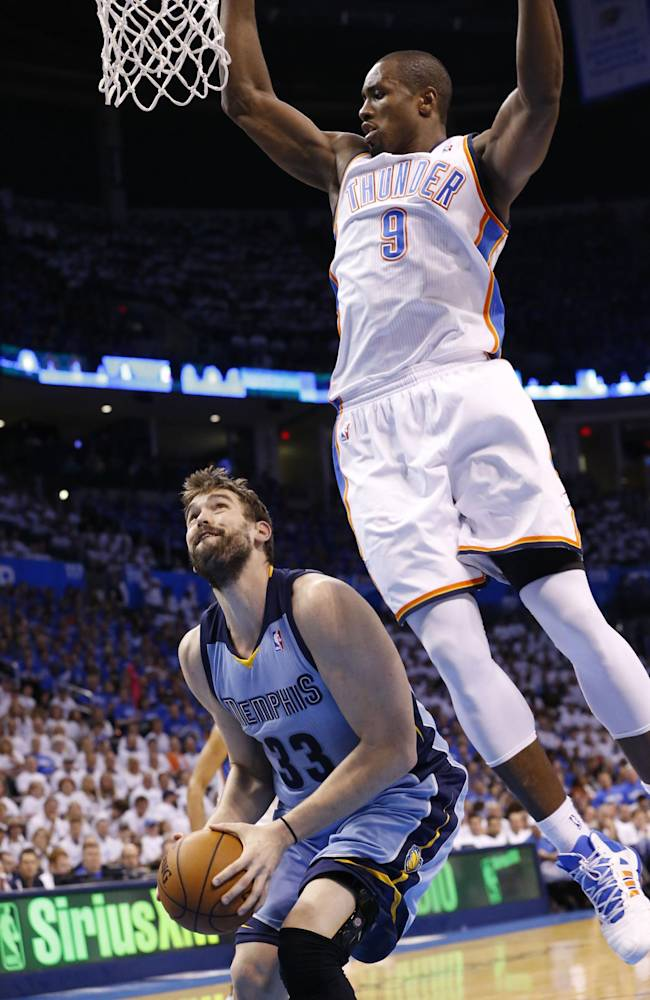 Oklahoma City Thunder forward Serge Ibaka (9) fouls Memphis Grizzlies center Marc Gasol (33) as Gasol prepares to shoot in the first quarter of Game 2 of an opening-round NBA basketball playoff series in Oklahoma City, Monday, April 21, 2014