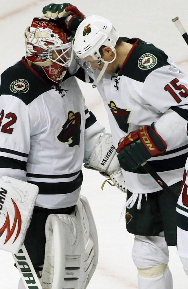 Minnesota Wild goalie Niklas Backstrom (32) celebrates with Dany Heatley (15) after the Wild defeated the Chicago Blackhawks 5-3 in an NHL hockey game in Chicago, Saturday, Oct. 26, 2013