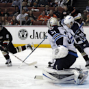 Anaheim Ducks center Mathieu Perreault (22) shoots the puck on Winnipeg Jets goalie Ondrej Pavelec (31), of the Czech Republic and defenseman Tobias Enstrom (39) with Ducks left wing Patrick Maroon in the second period of an NHL hockey game Monday, March