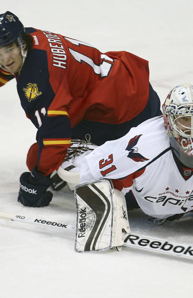 After blocking a shot-on-goal Washington Capitals goalie Philipp Grubauer (31) and Florida Panthers Jonathan Huberdeau (11) look for the puck during the second period of a NHL hockey game in Sunrise, Fla., Friday, Dec. 13, 2013