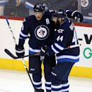 Winnipeg Jets' Blake Wheeler (26) celebrates with Zach Bogosian (44) after Wheeler scored against the Tampa Bay Lightning during the third period of an NHL hockey game Friday, Oct. 24, 2014, in Winnipeg, Manitoba The Associated Press
