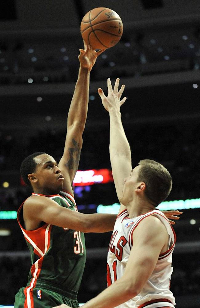 Milwaukee Bucks' John Henson left, goes up for a shot against Chicago Bulls' Erik Murphy right, during the second half of an NBA preseason basketball game in Chicago, Monday, Oct. 21, 2013. Chicago won 105-84