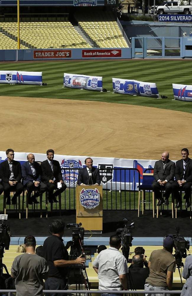 NHL Commissioner Gary Bettman, center at podium, speaks to the media during NHL hockey news conference Thursday, Sept. 26, 2013, at Dodger Stadium in Los Angeles, announcing the outdoor hockey game between the Los Angeles Kings and Anaheim Ducks. The game will be played on a temporary rink at the baseball field on Jan. 25, 2014