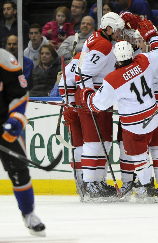 Carolina Hurricanes' Eric Staal (12), Nathan Gerbe (14) and Ryan Murphy (7) celebrate Jordan Staal's goal as New York Islanders' Frans Nielsen (51) stands in the second period of an NHL hockey game on Saturday, Oct. 19, 2013, in Uniondale, N.Y