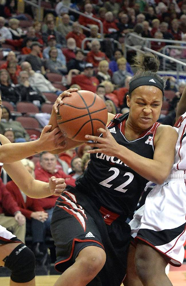 Cincinnati's Bianca Quisenberry, center, grabs a rebound away from the defense of Louisville's Shoni Schimmel, left, and Monny Niamke during the first half of an NCAA college basketball game Saturday Jan. 4, 2014, in Louisville, Ky