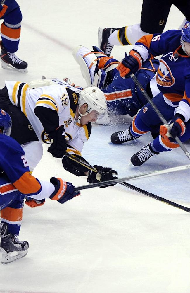 New York Islanders' Kyle Okposo (21) and Matt Donovan (46) block a shot on goal by Boston Bruins' Reilly Smith (18) in the first period of an NHL hockey game at the Nassau Coliseum on Saturday, Nov. 2, 2013, in Uniondale, N.Y