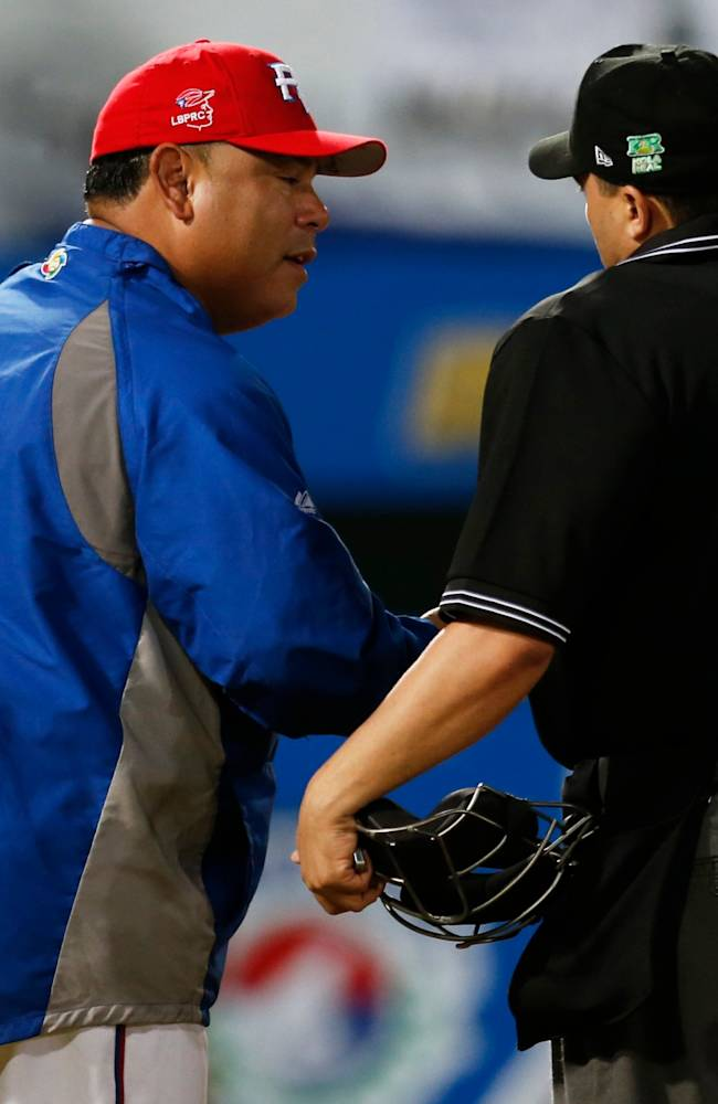 Puerto Rico's coach Carlos Baerga, left, argues with umpire Fernando Rodriguez from the Dominican Republic during a Caribbean Series baseball game against Venezuela in Porlamar, Venezuela, Wednesday, Feb. 5, 2014
