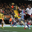 Fulham's Dimitar Berbatov, right, attempts a shot at goal past Aston Villa's Nathan Baker, center, and goalkeeper Bradley Guzan, left, during their English Premier League soccer match at Craven Cottage, London, Sunday, Dec. 8, 2013