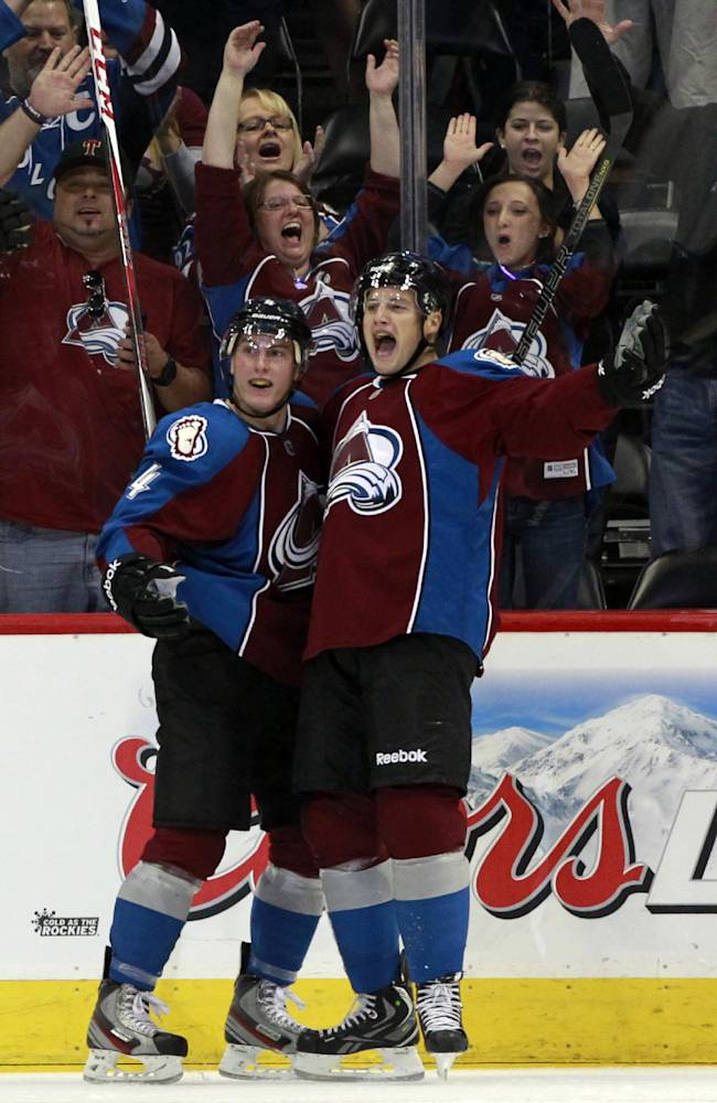 Colorado Avalanche defenseman Tyson Barrie, left, celebrates with center John Mitchell after his goal against the Anaheim Ducks in the second period of an NHL hockey game in Denver, Wednesday, Oct. 2, 2013