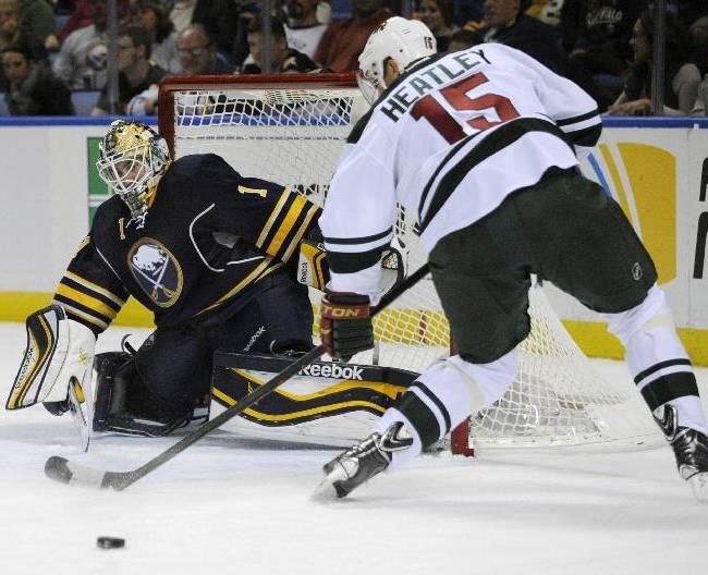 Buffalo Sabres goaltender Jhonas Enroth (1), of Sweden, slides across the goal crease while Minnesota Wild left winger Dany Heatley (15), of Germany, shoots the puck during the second period of an NHL hockey game in Buffalo, N.Y., Monday, Oct. 14, 2013